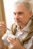 Senior mature man eat yogurt snack — Stock Photo
