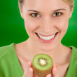 Healthy lifestyle - happy woman holding kiwi — Stok fotoğraf