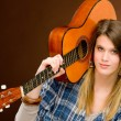Rock musician - fashion woman holding guitar — Stockfoto