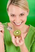 Healthy lifestyle - happy woman holding kiwi on green — Stock Photo