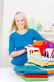 Laundry - woman folding clothes home — Stock Photo