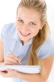 Happy student woman write notes on white — Stock Photo