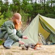 Camping woman tent cook food fire nature - Stock Photo