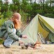 Camping woman tent cook food fire nature — Stock Photo