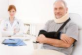 Senior patiënt gebroken arm in kantoor van arts — Stockfoto