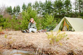 Camping woman tent sitting fire nature — Stock Photo
