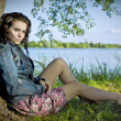 Beautiful young woman relaxing near river — Stock Photo