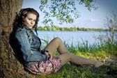 Hermosa joven relajante cerca de río — Foto de Stock