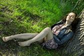 A beautiful girl sits near a tree — Stock Photo