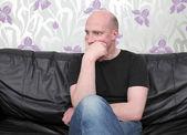 Pensamento de homem sofá chocado — Foto Stock
