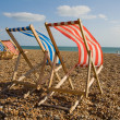Foto de Stock  : Deck chair sun lounger on beach windy day