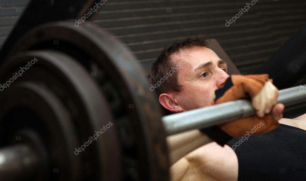 Bodybuilding workout in gym. Male lifting barbell. man under exercise equipment training upper body strength — Foto Stock #4574022