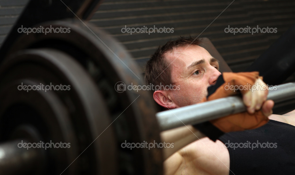 Bodybuilding workout in gym. Male lifting barbell. man under exercise equipment training upper body strength  Stockfoto #4574022