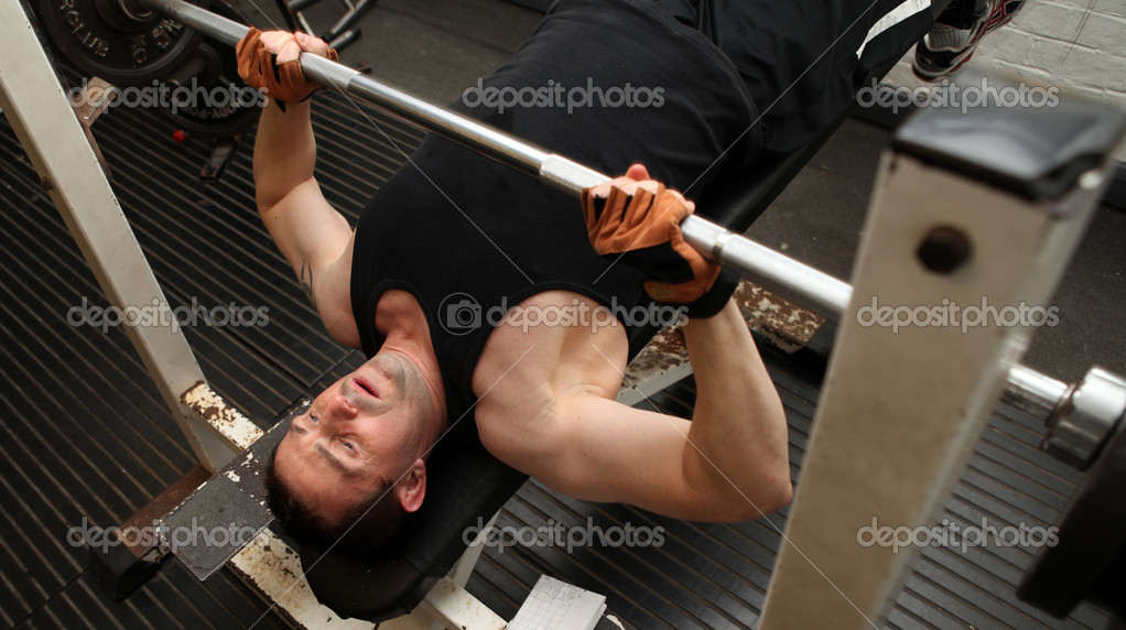 Bodybuilding workout in gym. Male lifting barbell. man under exercise equipment training upper body strength — Stock Photo #4574038