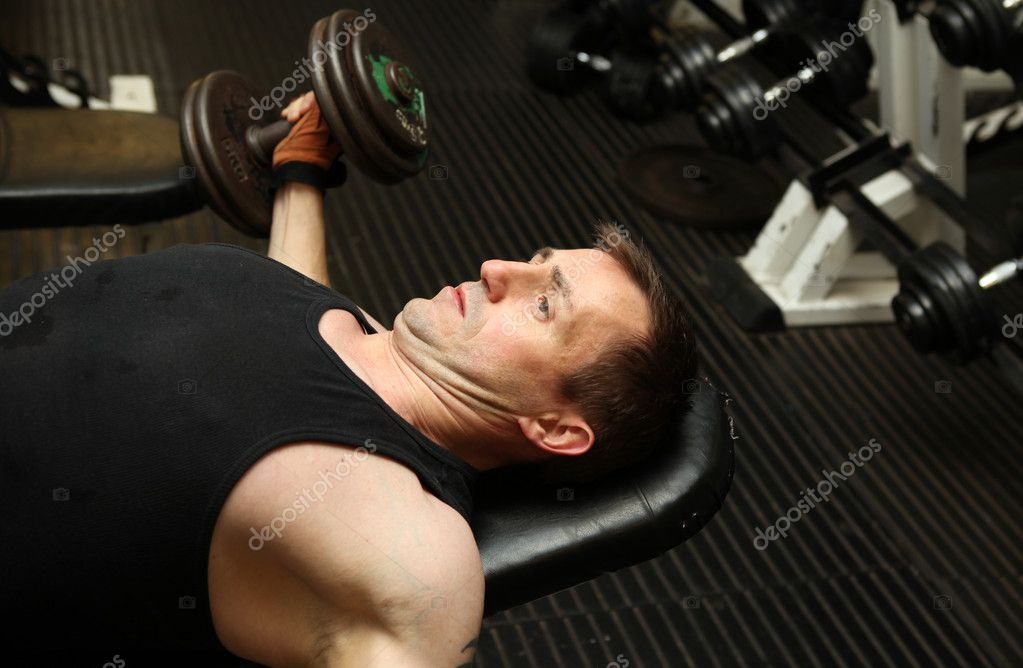 Training triceps with free weights. Male lifting dumbbell over head building muscle strength — Stock Photo #4574046