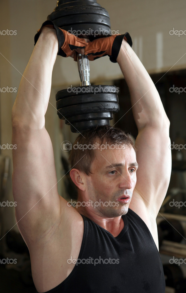 Training triceps with free weights. Male lifting dumbbell over head building muscle strength — Stock Photo #4574075