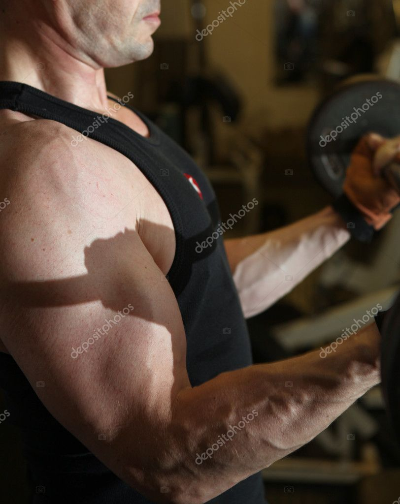 Bodybuilding workout in gym. Male lifting barbell. man under exercise equipment training upper body strength — Stock Photo #4574089
