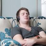 Relaxing sleeping in chair headphones — Stock Photo #4864531