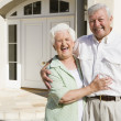 Senior couple standing outside house — Stock Photo #4752859