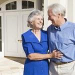 Senior couple standing outside house — Stock Photo