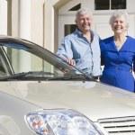 Senior couple standing to new car — Stock Photo