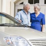 Senior couple standing next to car — Stock Photo