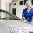 Senior woman standing next to new car — ストック写真
