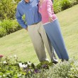 Senior couple standing in garden - Stock Photo