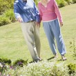 Senior couple walking in garden - Stock Photo