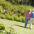 Senior couple walking in garden — Stock Photo