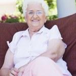 Senior woman sitting on garden chair — Stock Photo
