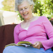 Senior woman reading book outside — Stock Photo #4752971
