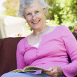Senior woman reading book outside - Stock Photo