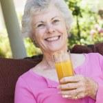 Senior woman enjoying glass of juice — Stock Photo