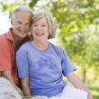Senior couple relaxing in park - Stock Photo