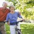 Senior couple on cycle ride -  