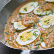 Eggs Cooked Moghali Style in a pan - Photo