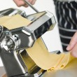 Fresh Egg Pasta being rolled in a Pasta Machine — Stock Photo