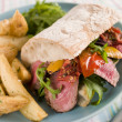 Steak and Roasted Pepper Ciabatta Sandwich with Spiced Potato We - Lizenzfreies Foto