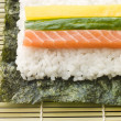 Making Rolled Sushi in a Sushi Mat - Stock Photo