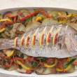 Whole Roasted Bream with Chilies Potatoes and Peppers - Stock Photo