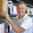 Senior man pulling a library book off shelf — Stock Photo #4754254