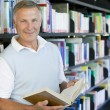 Senior man reading in a library — Stock Photo #4754257