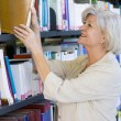 Senior woman pulling a library book off shelf — Stock Photo