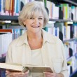 Senior woman reading in a library — Stock Photo