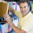Man pulling a library book off shelf — Stok fotoğraf