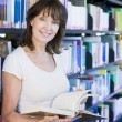 Woman reading in a library — Stock Photo