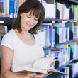Woman reading in a library - Foto Stock