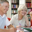 Adult students working together in a library — Stock Photo #4754280