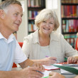 Adult students working together in a library — Stock Photo #4754281